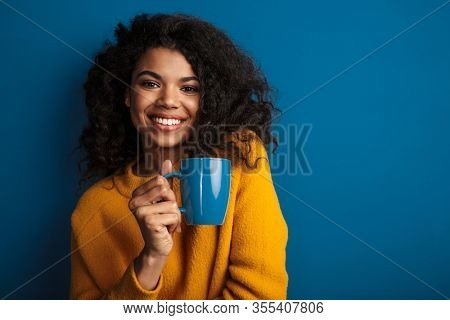 Photo of a pleased young african woman posing isolated over blue wall background drinking tea.
