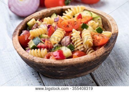 Bowl of fusili pasta salad with fresh vegetables