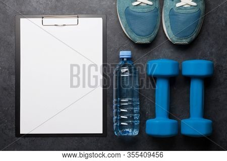 Fitness equipment and blank sheet for workout plan on a stone background. Top view flat lay with copy space