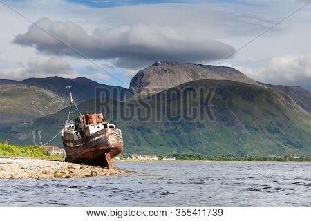 Ben Nevis.  The View Across Loch Linnhe Beyond An Abandoned Boat Towards Ben Nevis, The Highest Moun