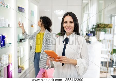 Pretty Beauty Consultant In A White Blouse Holding A Tablet