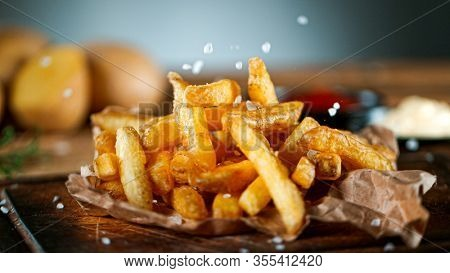 Freeze Motion Shot of Falling Fresh French Fries on Wooden Table and Adding Salt