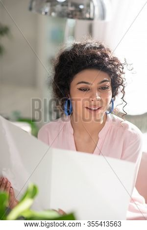 Beautiful Curly-haired Woman Looking Trough The Price List And Looking Involved