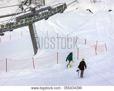 Snowboarders Freeriders Climb Up The Mountain Under The Cable Car On The Ski Resort