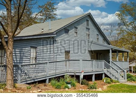 An Old Grey Wood Siding House With A Wheelchair Accessible Ramp
