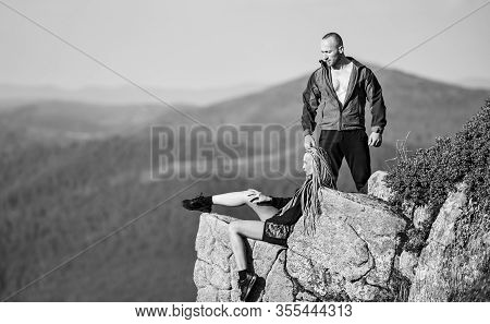 Tourist Hiker Girl And Man Relaxing. Hiking Benefits. Hiking Weekend. On Edge Of World. Woman Sit Ed