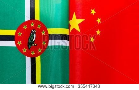 Fragments Of The National Flags Of The Commonwealth Of Dominica And China Close Up