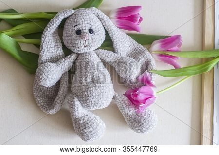 Knitted Light Gray Handmade Crafted Rabbit With Pink Tulips .