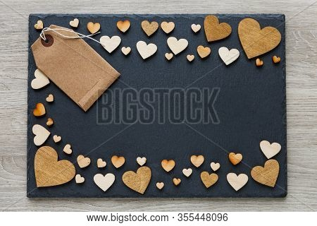 Wooden Hearts Are Beautifully Placed On A Dark Board. Place For Text. Frame With Hearts With Tag And