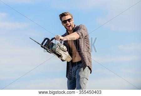 Handsome Man With Chainsaw Blue Sky Background. Gardener Lumberjack Equipment. Sharp Blade. Dangerou