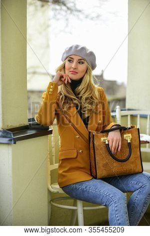 Looking Trendy. Fashion Brunette Model In Nice Clothes. Wearing Jacket And Hold Handbag. Style Blond