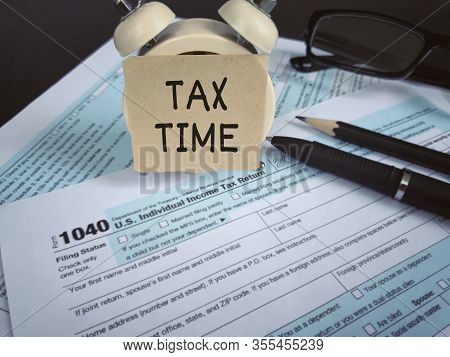 Tax-filling Concept - Tax Time Written On A Paper, A Pencil, A Pen, Eyeglasses And Featuring Half Of