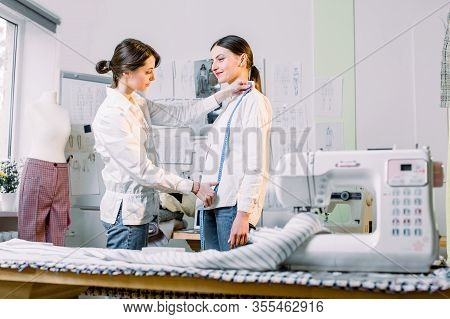 Pretty Young Female Tailor Measuring Her Client Woman To Make Stylish Clothes In Her Dressmaker Stud