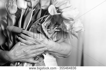 Hands Of A Senior Woman Holding Flower Bouquet. Idea Of A Mother's Day Greeting Card, Women's Day Or