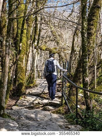 In The Winter Senior Man With A Backpack And In A Baseball Cap Is Walking Along A Hiking Stone Trail