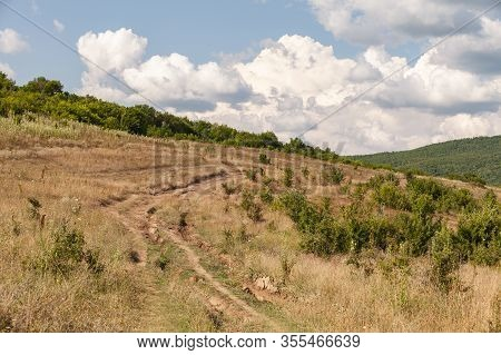Empty Dirty Rural Road In Bad Condition. Crimean Mountains At Sunny Day, Landscape Photo Background