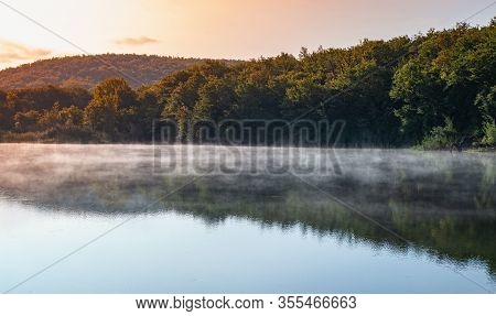 Coastal Morning Landscape With Forest And Fog Layer Over Still Lake Water In Crimean Mountains