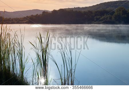 Morning Landscape With Reed And Fog Layer Over Still Lake Water In Crimean Mountains