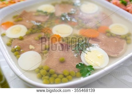 Jellied Meat With Beef Tongue, Peas, Carrots, Herbs. A Dish On The Table For A Celebration. Cold App