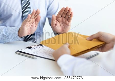 Businessman refusing to receive the money in a brown envelope to sign a business contract ,Anti brib