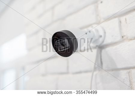 Surveillance Ip Camera Mounted On The White Brick Wall Indoors. Home Video Surveillance Concept