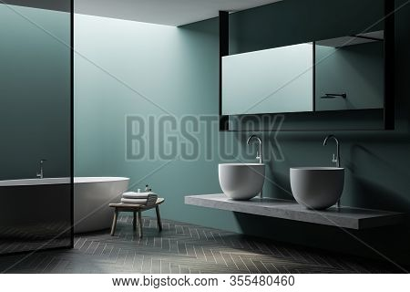 Corner Of Spacious Bathroom With Green Walls, Dark Wooden Floor, Comfortable White Bathtub, Glass Wa
