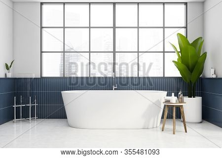 Interior Of Modern Bathroom With White And Blue Tiled Walls, White Floor, Comfortable White Bathtub