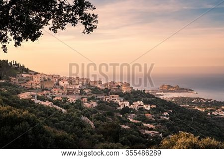 Dusk Falling Over The Village Of Monticello In The Balagne Region Of Corsica With The Red Rock Of Il