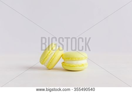 Yellow Franch Macarons On A White Wooden Background. Lemon Macarons. Place For Text.