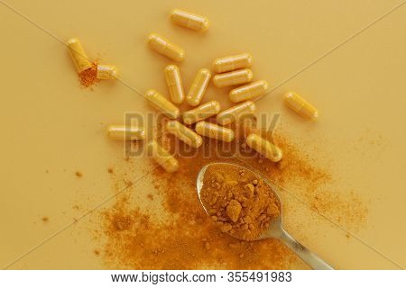 Curcumin Capsules With Turmeric Powder Against Yellow Background.