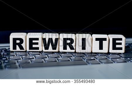 Concept Word Rewrite On Cubes Against The Background Of Laptop Keys
