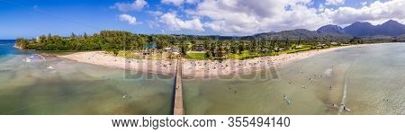 Aerial Panoramic Image Off The Coast Over Hanalei Bay And Pier On Hawaiian Island Of Kauai With Surf