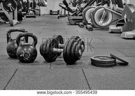 Dumbbells And Kettlebells On The Background Of The Gym. Bodybuilding Equipment. Fitness Or Bodybuild