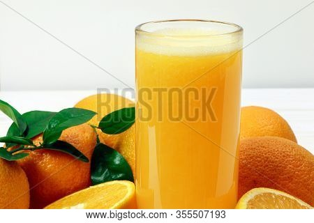 A Glass Of Fresh Orange Juice And Orange Fruits On A Wooden Table. Healthy Food