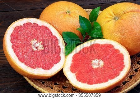 Grapefruit Fruits On A Wooden Table. Healthy Food. Brown Background. Grapefruits On A Tray.