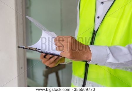 Foreman Builder, Engineer Or Inspector In Green Safety Vest Reflective Checking And Inspecting With