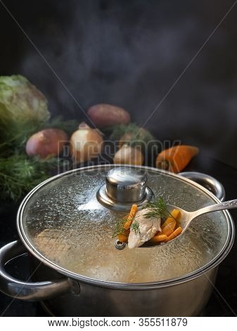 Soup With Meat And Vegetables Is Cooked In A Saucepan. Saucepan With Lid. In A Spoon Lies Meat With