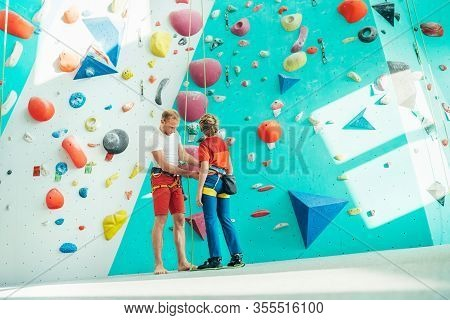 Father Helping His Teenage Son And Checking Climbing Harness Near The Indoor Climbing Wall. Boy Prep