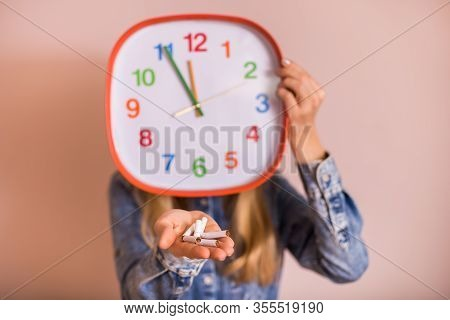 Woman Holding Broken Cigarettes And Clock In Front Of The Wall.quitting Smoking Concept.focus On Cig