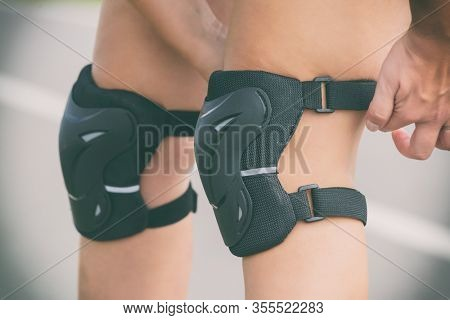 Woman rollerskater putting on knee protector pads on her leg