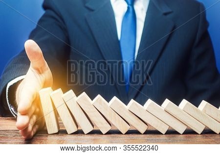 Businessman Stops Domino Falling With His Palm. Strategy Development. Debt Restructuring. Risk Manag