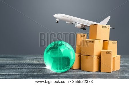 Light Green Globe Near Cardboard Boxes And Freight Plane. International Delivery Of Goods And Produc
