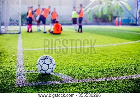Soccer Ball On Green Artificial Turf At Corner Of Football Field With Blurry Players Background,