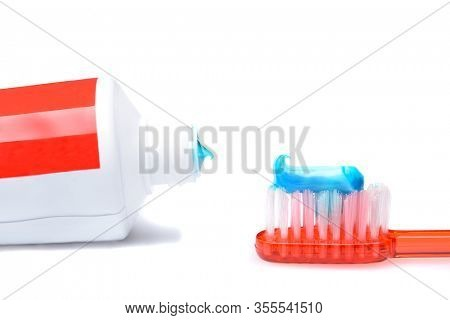 Oral Hygiene Concept: Closeup of a tube of toothpaste and a toothbrush with a dollop of paste isolated on white with slight shadow.