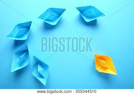Group Of Origami Boats On Blue. One Orange Paper Boat With A Group Of Blue Boats On Blue. Team Work