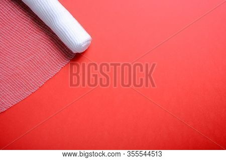 Sterile Bandage On Red Background.  Roll Of Bandage.