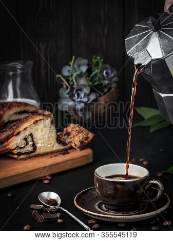 Espresso Is Poured From A Coffee Pot Into A Black Coffee Cup. In The Background Is A Loaf Of Chocola