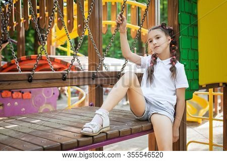 Lovely Small Thoughtful Girl Sitting At The Playground. Concept Of Summer, Childhood And Leisure.