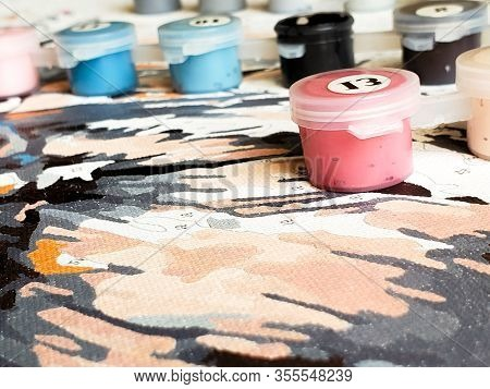 Painting On Canvas By Numbers And Numbered Jars Of Paint On The Background Of The Canvas.
