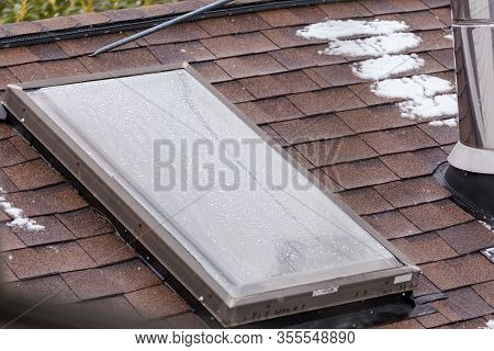Sky Light Or Skylight With Snow And Frost. Cold Weather Photo Of Home With Sky Light In Roof.
